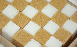 White and brown sugar cubes close-up chess background. White and brown sugar cubes in box close-up background Royalty Free Stock Photography