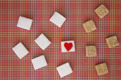 White and brown sugar cubes with a red heart on one of them. Top view. Diet unhealty sweet addiction concept Stock Image