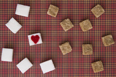 White and brown sugar cubes with a red heart on one of them. Top view. Diet unhealty sweet addiction concept Royalty Free Stock Images