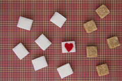 White and brown sugar cubes with a red heart on one of them. Top view. Diet unhealty sweet addiction concept Stock Images