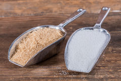 White and brown sugar in metal shovels Royalty Free Stock Photos