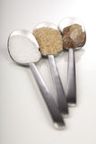 White and brown sugar on spoons Stock Images
