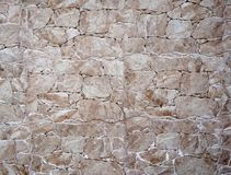White and brown wall made of irregular polished stones. Background and texture Stock Photography