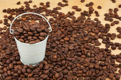 White bucket with coffee beans  on the wooden floor Royalty Free Stock Images