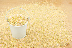 White bucket with millet on the wooden floor Stock Photos