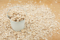White bucket with oat flakes  on the wooden floor Royalty Free Stock Image