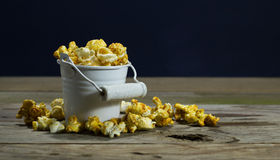 White bucket with popcorn. On wooden background stock photo