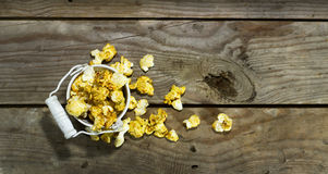 White bucket with popcorn. On wooden background royalty free stock images