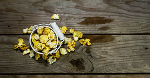 White bucket with popcorn. On wooden background stock images