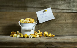 White bucket with popcorn. On wooden background stock photography