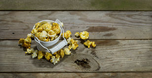White bucket with popcorn. On wooden background stock photos