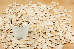 White bucket with pumpkin seeds  on the wooden floor Royalty Free Stock Photo