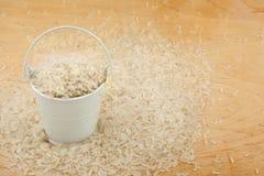 White bucket of rice on the wooden floor Stock Photo