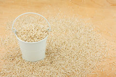 White bucket with sesame seeds  on the wooden floor Stock Image