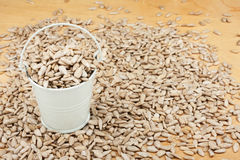 White bucket with sunflower seeds  on the wooden floor Stock Photo