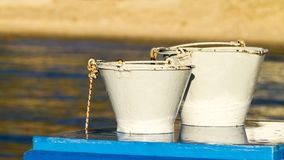 White buckets on blue table Royalty Free Stock Photography