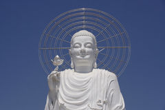 White Buddha. Vietnamese smiling white buddha statue, with eyes half-opened, a lotus flower in the hand, mettalic aura, blue sky in background Royalty Free Stock Images