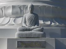 Buddha: white stone figure meditating Royalty Free Stock Photography