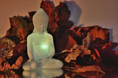White buddha in front of colourfull Autumn leafs Royalty Free Stock Photos