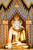 White Buddha with golden crown and robe between color columns Stock Image