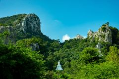 White Buddha Image on hill surrounded by trees. Thailand stock images