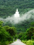 The white Buddha image on the mountain Royalty Free Stock Images