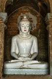 White Buddha marble in meditation posture with golden third eye. The meditating sculpure is sitting in meditation posture in a cave from bricks. The buddha is royalty free stock photos