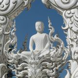 White Buddha meditating being detached on the blue sky surrounded by white ornaments stock photography