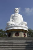 White Buddha statue sitting in lotus flower Stock Photos