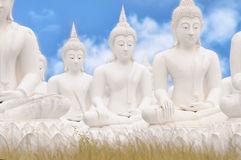 White Buddha statues. On blue sky background Royalty Free Stock Photos