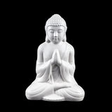 White Buddha Statuette. White, porcelain statuette of sitting meditating Buddha isolated on black Stock Images
