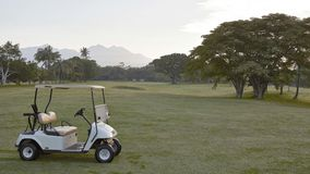 White buggy on golf course. White electric golf buggy parked on the fairway of the golf course at Lombok, Indonesia with Rinjani Mountains visible through the royalty free stock photo