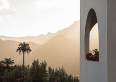 White building with arch window with plants, palm trees and mountains in the background. Arch window with plants, and palm trees and misty mountains in the Stock Photos
