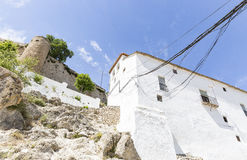 White building with electric cables and the ancient castle of Moclin, Granada, Spain Royalty Free Stock Images