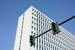 White building with a green traffic light in the foreground stock photography