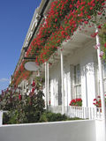 White buildings in flower. A row of white buildings with beautiful red flowers hanging from the balconies stock image