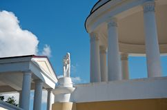 White buildings in neoclassical architectural style with columns and a statue. Against a blue sky stock photography