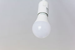 White bulb hanging on white ceiling. The white bulb hanging on white background and not lit royalty free stock images