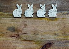 White bunnies on wooden background copyspace. White esater bunnies lined up at the bottom of wooden copyspace, facing opposite directions - easter background Stock Photos