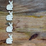White bunnies on wooden background copyspace. White esater bunnies lined up at the side of wooden copyspace, facing the same direction - easter background Royalty Free Stock Photos