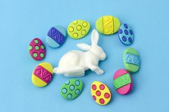 White bunny and colorful easter little eggs. On blue background. Easter decoration stock photography