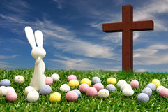 A white bunny, easter eggs and a cross. 3D illustration. A white plastic bunny figurine displayed with speckled easter eggs and a wooden cross Royalty Free Stock Photography