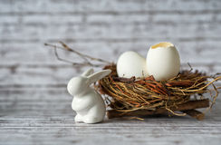 White Bunny Porcelain Besides Eggs in a Nest. Close up White Bunny Rabbit Porcelain Besides Easter Eggs in a Nest on Top of a Table with Fuzzy Background royalty free stock photo