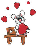 White bunny sits on a bench and holding a heart Stock Photos
