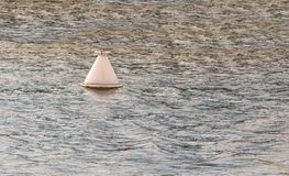 White buoy  on a background of water of a steel color lighthouse on a smooth Royalty Free Stock Images