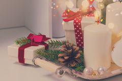 Burning advent candles. White burning advent candles with christmas decorations and christmas gift boxes on table, retro toned Royalty Free Stock Images