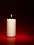 White burning candle. Closeup of single white burning candle on red background Stock Image