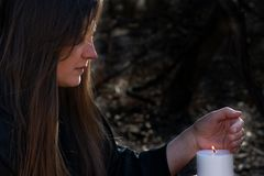 Free White Burning Candle In Woman`s Hands In The Middle Of The Forest. Hope And Pray Concept. All Saints Day Celebration. Witchcraft Royalty Free Stock Photography - 166683797