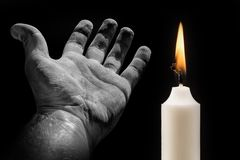 Hand and candle on a black background on the subject of death stock image