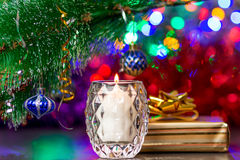 White burning candle under branch of christmas tree with decoration Royalty Free Stock Images